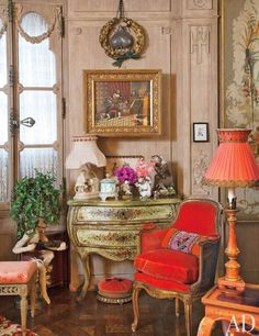 An 18th-century Venetian bombé chest in the living room of Iris Apfel's Manhattan apartment sits next to a red velvet arm chair, which adds a pop of vibrant color to the space. | archdigest.com