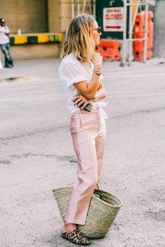 Camisa branca com nó na cintura, calça de cetim rosa, bolsa de palha, mule flat com animal print