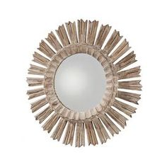 Sunburst wall mirror with a hand-carved wood frame.   Product: Wall mirror Construction Material: Wood and mirrored glass  Color: Whitewashed wood  Features:   Starburst shape Arrow-like rays Hand-carved    Dimensions: 20.5 Diameter