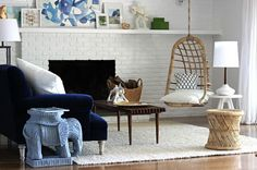 living room by Emily Henderson, navy blue velvet sofa, rattan hanging chair, white brick fireplace, wicker elephant