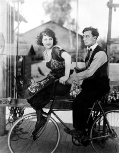 Buster Keaton & Sybil Seely riding a bicycle.