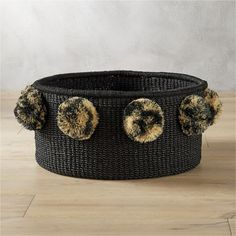Shop button pom pon basket.   Simple woven round delights with an extra dose of whimsy.  Crafted from black abaca, closed weave basket shapes up a simple silhouette with a fun surprise––eight black and natural raffia pom pons.