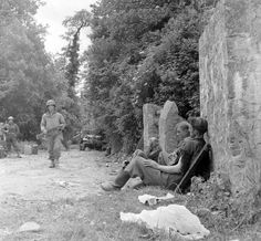 American forces advancing towards Ste. Mere Eglise, past what appear to be German prisoners resting along side of road, following Normandy invasion during WWII.