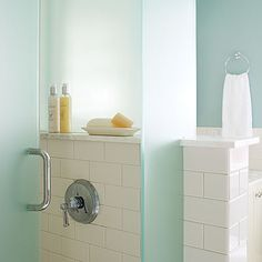 The blue tint of the frosted-glass shower surround stays in step with the wall color, while the translucency of the glass allows light into the shower and adds to the open feel. The half-wall creates the perfect shelf for pampering products.  Reflective and high-gloss materials—like the off-white subway tiles on the vanity backsplash and shower wall—further amplify natural light.