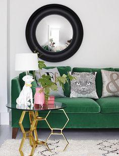 Joli salon avec un canapé vert bouteille et des coussins imprimés. Les pieds de la tables basses en forme hexagonale doré avec une lampe chien en céramique joanna henderson