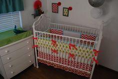 Hot Pink Chevron crib skirt with pom pom trim and bright green and aqua fabrics in the nursery