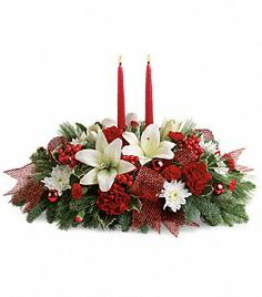 Capture the magical spirit of the holidays with this gorgeous centerpiece of white Asiatic lilies, red carnations and fresh holiday greens accented with a holiday ribbon, red ornaments and luminous candles.