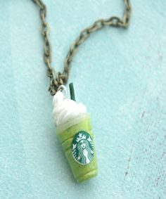 """this necklace features a miniature green tea frappe pendant sculpted from polymer clay. it measures about 2 cm tall and is securely attached to a 24"""" bronze chain necklace with lobster clasp closure."""