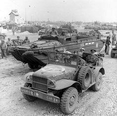 """Le 12 juin 1944, sur la plage du Ruquet à Saint Laurent sur Mer, secteur Omaha. La plage est encombrée de véhicules, à gauche la villa """"L'Abri Côtier"""" avec sa plateforme en bois sur le toit. d'autres photos de la villa l'Abri Côtier: www.flickr.com/photos/tags/abricotier Noter le Dukw codé X32 visible sur d'autres photos. Dans un Dodge WC 56 Command Car, devant à gauche: le Lt-col. James Frederick Gault, le British military assistant d'Eisenhower..."""