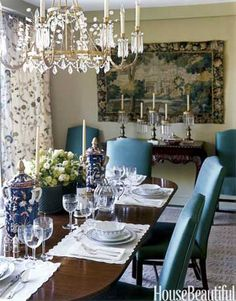 Warm dining room- Blue upholstered chairs, linen walls, crystal and gilt chandelier with dark table
