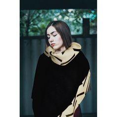 Elegante poncho nero con inserti laterali e collo alto color cammello a disegni geometrici.