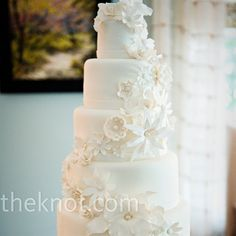 Pure white sugar flowers were wrapped around the cake's six eggshell-colored tiers. Holly thought she wanted a typical bride's cake but, after a tasting, she was hooked on a Grand Marnier butter cake with blackberry filling.