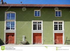 Green Traditional Swiss Building With Red Doors Stock Photo - Image of world, fountain: 99024052 Old World, Switzerland, Fountain, Garage Doors, Windows, Stock Photos, Traditional, Building, Outdoor Decor