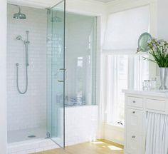 Douche à l'italienne dans salle de bain blanche. carrelage douche et peinture blanc. Receveur douche sur socle surélevé