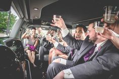 Photo of bridal party limo ride, toasting in the limousine. Group cheers with bride and groom