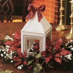 "Nostalgic Lantern Plastic Canvas ePattern - Add a bit of nostalgia to your Christmas celebration with this old-timey ""lantern."" When placed amid a bright spray of poinsettias and accented with a cheery bow, the design becomes a festive centerpiece. The design is stitched using worsted weight yarn, white/gold cord, and 7 mesh plastic canvas. Number of Designs: 1 centerpiece Approximate Design Size: 5-1/4""w x 9-3/4""h x 5-1/4""d"