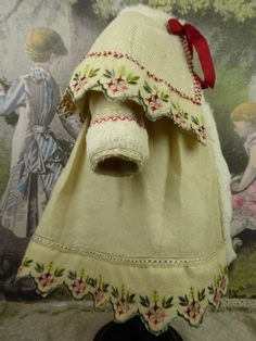 This French three-piece antique dolls ensemble consists of a wool Christmas coat, faux-fur bonnet and faux-fur muff. Antique wool forms the basis