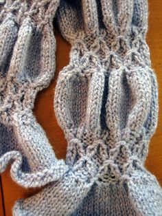 Knitted in a smocking pattern that creates ruches between the smocks, this pattern is fun to knit.  The wavy silhouette gives the scarf lots of places to interlock, creating a nice snug fit for a cold winter day—or night!