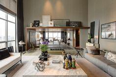 Desenhado pelo arquiteto João Armentano, o grande Living, com pé direito duplo de sete metros de altura, conta com uma área de estar e um escritório (ao fundo). Mostra Black 2013.
