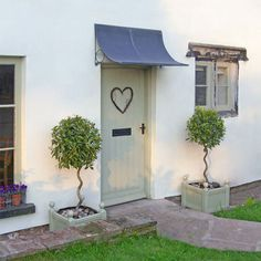 This is my favourite exterior ~ the door colour with a heart on, and the planters.