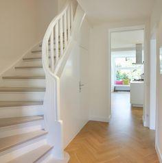 Der Flur mit Treppenaufgang bekam mit dem Umbau seine Eleganz zurück. Das Fischgrätparkett ist von 2015, die Holztreppe von 1932. Ihre Stufen sind weiß...