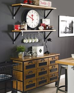 A bold black-painted wall makes a dramatic background, while highlighting the rich golden tones of the vintage multi-drawer dresser and utilitarian shelves. Add a carefully curated selection of vibrant accessories to lift help the mood.