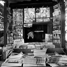 "Vivian Maier. March 1954.  The Time magazine is the March 22, 1954, issue, headlined ""McCarthy and His Men"" and featuring Roy Cohn. Groucho Marx is of course on the cover of that TV Guide (the March 19-25 issue). The World-Telegram is the newspaper in the foreground. Life is the March 22, 1954, issue, with the head of an emperor penguin barely showing. (Won't go on anymore!)"