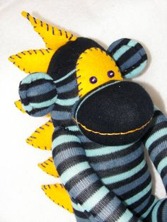 """Sock Monkey Dinosaur Doll Plush Toy - in Blue Stripes with Yellow Dinosaur Spikes. This monkey measures in at approximately 15"""" from head to toe (does not include the height of his top spike), and his tail measures 12"""". What a cute and unique gift for someone important in your life!! www.DebBixler.com"""
