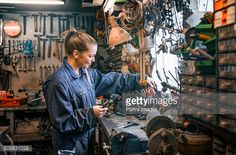 Stock Photo : Female motor mechanic at work at the work shop.