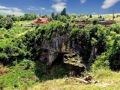 God's Bridge (Ponoarele, Mehedinti Country). It is a natural bridge formed when the ceiling of a cave had collapsed and supports a natural road 6 m wide, which is used by cars and heavy vehicles.