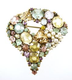 Dorrie Nossiter. Arts and Crafts pearl and gemset brooch, c. 1930s, inverted teardrop shape set with seed pearls and coloured gemstones of varying sizes dispersed with gilded fleurs-de-lys motifs, set in silver, length 5.4 cm. Sold by Byrne's Fine Art Auctioneers. View 1.