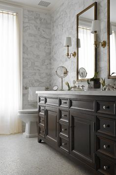 Stunning master bath features brass mirrors on white marble subway tiled backsplash flanked by antique brass sconces over chocolate brown double vanity topped with contrasting white marble and his and her sinks atop mosaic marble floor.