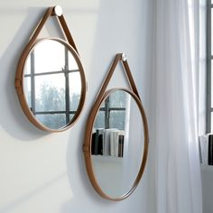 George large hanging round mirror features leather wrapped steel frame with buckle strap and stainless steel hanging hardware.