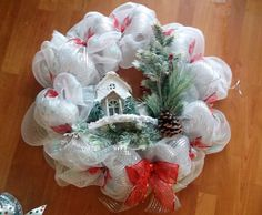 A winter cottage is surrounded in pines and snow in this gorgeous white deco mesh wreath accented with red ribbons.