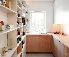 Kjøkkenet har åpne hyller på den ene siden og lukkede skap på den andre