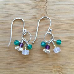 """These amethyst, green onyx, rainbow Moonstone,and citrine earrings are inspired by the crocus, that first spring flower! Petite clusters of gemstones, each wire wrapped by hand with sterling silver wire, swing from a delicate link of twisted sterling silver. The earrings drop 1"""""""