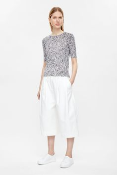A simple, short-sleeved style, this top is made from finely knitted cotton with an all-over mottled print. Slightly cropped, it has a classic round neckline and tightly ribbed hemline.