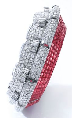 Www.ambragold.com An Important Art Deco Ruby and Diamond Bangle-Bracelet, by Boucheron, circa 1935. Of hinged design, one side decorated with calibré-cut rubies in concealed settings, the other pavé-set with brilliant-cut and baguette diamonds, signed Boucheron, French assay and maker's marks, #ArtDeco #Boucheron #bangle #bracelet