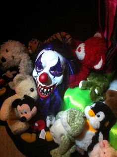 Scary clown mask surrounded by carnival prizes in clown hallway....
