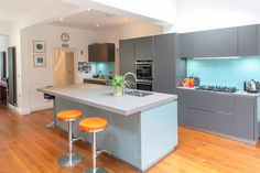 Total property refurbishment in Twickenham by L&E (Lofts and Extensions) - don't move extend. 1930s semi. Wooden floor, Grey kitchen, orange barstools, glass splashback