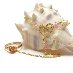 This pretty and delicate slave bracelet is adorned with a cute gold filigree heart at its center, shaped by hand, & surrounded by light, rosy pink