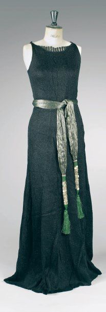 Paul Poiret, circa 1929 -   evening dress in black linen jersey sometimes included abstract patterns, high boat neck highlighted w/ a net, American armholes, flowing skirt worked diagonally highlighted by a border at the waist.