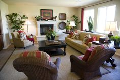 Here we have a room featuring a red and tan color combination, offset by green plants throughout the room. Wicker chairs and black coffee table add a dark flourish.