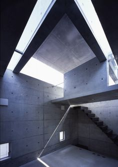 """Depicted here is a bedroom, made from concrete and lit by natural lighting from the small square windows and one large one, similar in the way the bedroom at """"House at Big Hill"""" was designed."""