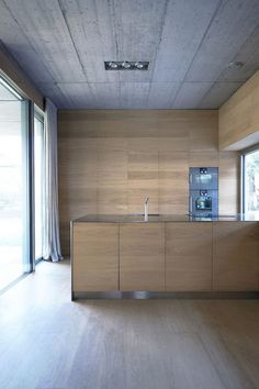 Oman and his partner Andrej Gregoric had the cupboards, stairs, and bed all custom-made. The interior casework provides storage and adds warmth to the concrete walls.       Courtesy of Tomaz Gregoric.