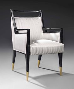 GIO PONTI (1891-1979) ARMCHAIR, CIRCA 1950 produced by Cassina, lacquered ebonised wood, brass sabots and upholstery 35 in. (89 cm.) high; 22 7/8 in. (58.2 cm.) wide; 21¼ in. (54 cm.) deep