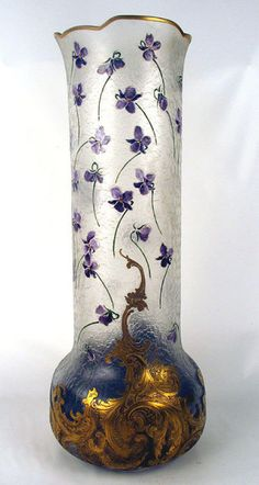 Monumental Mont Joye Cameo Glass Vase, Early 20th Century, Art Nouveau. Compressed globular base with elaborate gilt painted cameo acid etched scroll work border interspersed with silver roses. Long cylindrical neck scattered with enameled violet buds on the acid cut textured ice chipped ground, a raised gilt foliate rim. Gilt Mont Joye bishop insignia mark / http://www.antiques.com/classified/Antique-Glass-/Antique-Glass-Vases/MONUMENTAL-MONT-JOYE-CAMEO-GLASS-VASE-VIOLETS-ART-NOUVEAU#