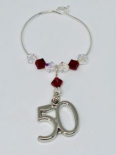 Garnet Wine Glass Charm - set with a silver plated 50 charm - finished with Garnet and Clear Swarovski Crystals Garnet is the birthstone for January Wine Glass Charms, Organza Bags, Birthstones, Garnet, Silver Plate, Swarovski Crystals, 50th, January, Charmed