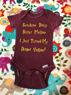 """CALLING ALL HARRY POTTER FANS! This onesie is super cute for any Harry Potter fanatic and is sure to get chuckles by anyone who reads it! """"Sunshine, Daisy, Butter Mellow, I Just Turned My Diaper Yellow!"""" Color: Burgundy with Yellow Lettering 100% cotton Made using a plain Gerber"""