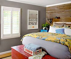 A distressed wooden wall add major style to this pattern-filled bedroom. Get decorating ideas with our DIY headboards: http://www.bhg.com/rooms/bedroom/headboard/cheap-chic-headboard-projects/?socsrc=bhgpin022713woodwall